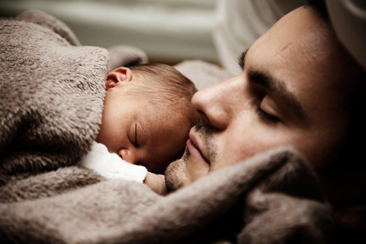 Sovende spædbarn med far